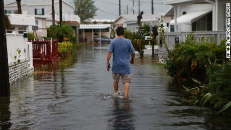 A resident of the Sandpiper Resort in Holmes Beach, Florida surveys the rising water coming from the Gulf of Mexico into his neighborhood as winds and storm surge associated with Tropical Storm Hermine impact the area on September 1.