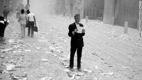 USA. NYC. 9/11/2001. A dazed man picks up a paper that was blown out of the towers after the attack of the World Trade Center, and begins to read it..