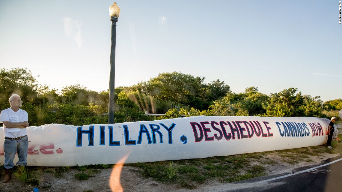 """Protesters stand on the side of the road with an inflatable marijuana cigarette as a motorcade carries Hillary Clinton to a fundraiser in Southampton, New York, on Sunday, August 28. The Democratic presidential nominee <a href=""""http://www.cnn.com/2015/11/07/politics/hillary-clinton-marijuana/"""" target=""""_blank"""">has said she wants to downgrade marijuana as a Schedule 1 substance</a> so that more people can do research on its medical benefits. Marijuana is currently categorized by the Drug Enforcement Administration as a Schedule 1 drug, the highest categorization for drugs """"with no currently accepted medical use and a high potential for abuse."""""""