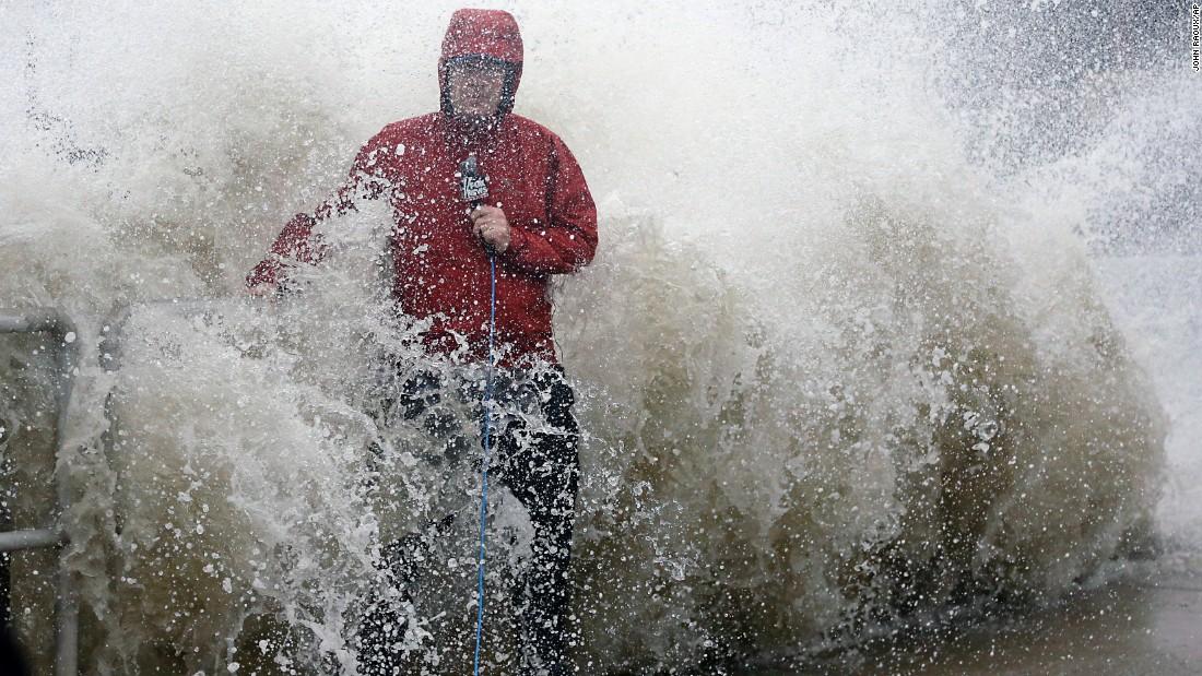 A news reporter works near a sea wall in Cedar Key, Florida, as Hermine neared the coast on Thursday, September 1.