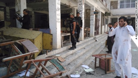 Pakistani police officials inspect the site of a suicide bomb attack at a district court in Mardan.