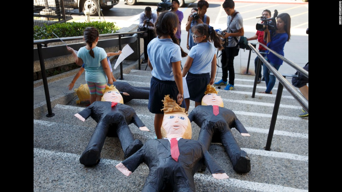 Children in Norwalk, California, drag Donald Trump piñatas down stairs Wednesday, August 31, as they encourage Latinos to register to vote against the Republican presidential nominee.