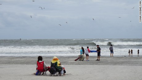 Beachgoers endure high winds and flying sand on Labor Day weekend at Atlantic City.