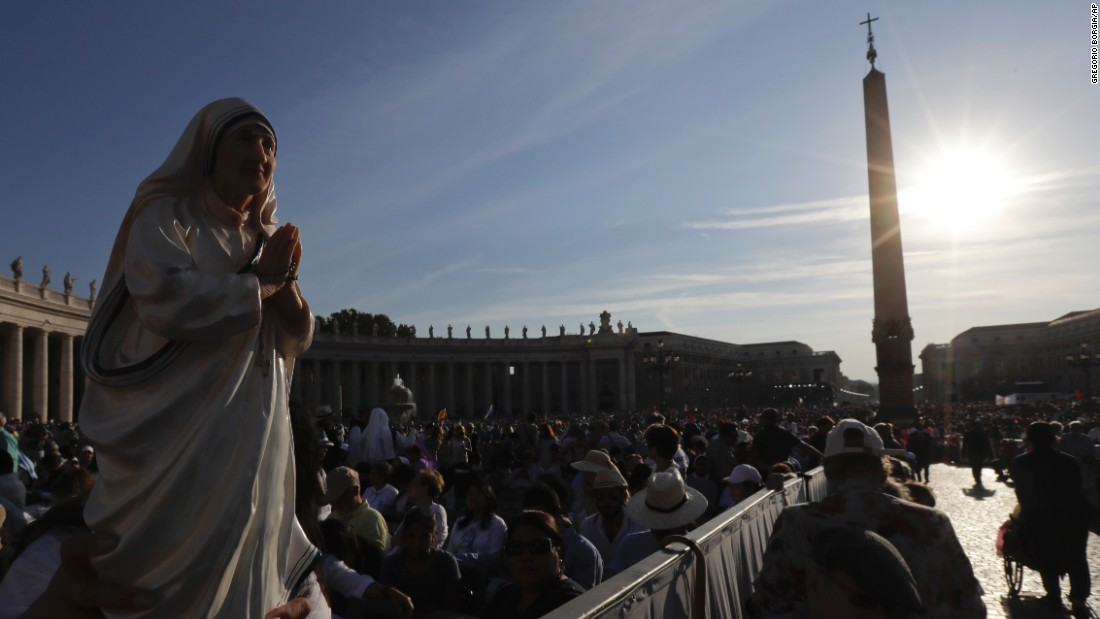 Irma Escuero, of New York, holds a statue of Mother Teresa before the start of Mass celebrated by Pope Francis at the Vatican.