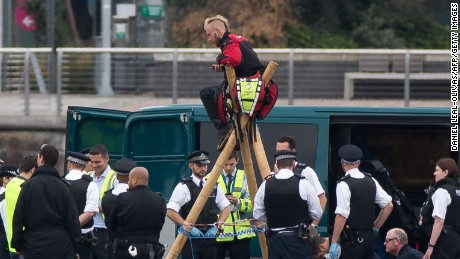 """Emergency services surround protestors from the movement Black Lives Matter after they locked themselves to a tripod on the runway at London City Airport in London on September 6, 2016. Flights at London City Airport have been delayed after Black Lives Matter protesters crossed the dock and """"occupied"""" the runway. / AFP / DANIEL LEAL-OLIVAS        (Photo credit should read DANIEL LEAL-OLIVAS/AFP/Getty Images)"""
