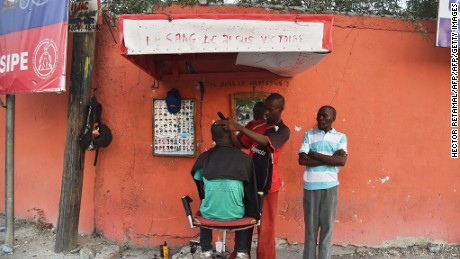 A man get his hair cut on by a barber on Delmas street in Port-au-Prince on August 22, 2016. / AFP / HECTOR RETAMAL        (Photo credit should read HECTOR RETAMAL/AFP/Getty Images)