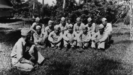 A Marine Corp unit comprised of Navajo Indians sits on the grass in uniform, Peleliu, November 1944.  Front L to R: Billy Cleveland, Nelson A. Brown, Alfred Tah, San Tsosie, Alex Williams.  Rear L to R: Dennis Cattlechaser, Thomas Claw, Joe Kellwood., Carl Crawford, Wallace Peshlakai, Layne Paddock.  In the foreground is marine Lieutenant Colonel James C. Smith. (Photo by U.S. Department of Defense/CNP/Getty Images)