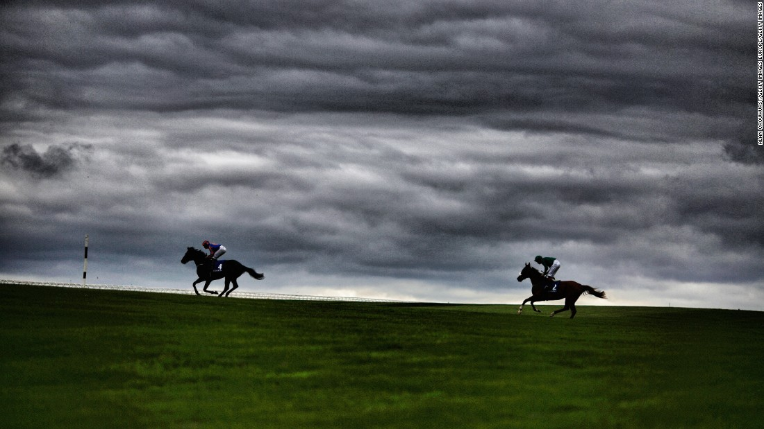Runners make their way across the center of the track for the start of another Curragh race.