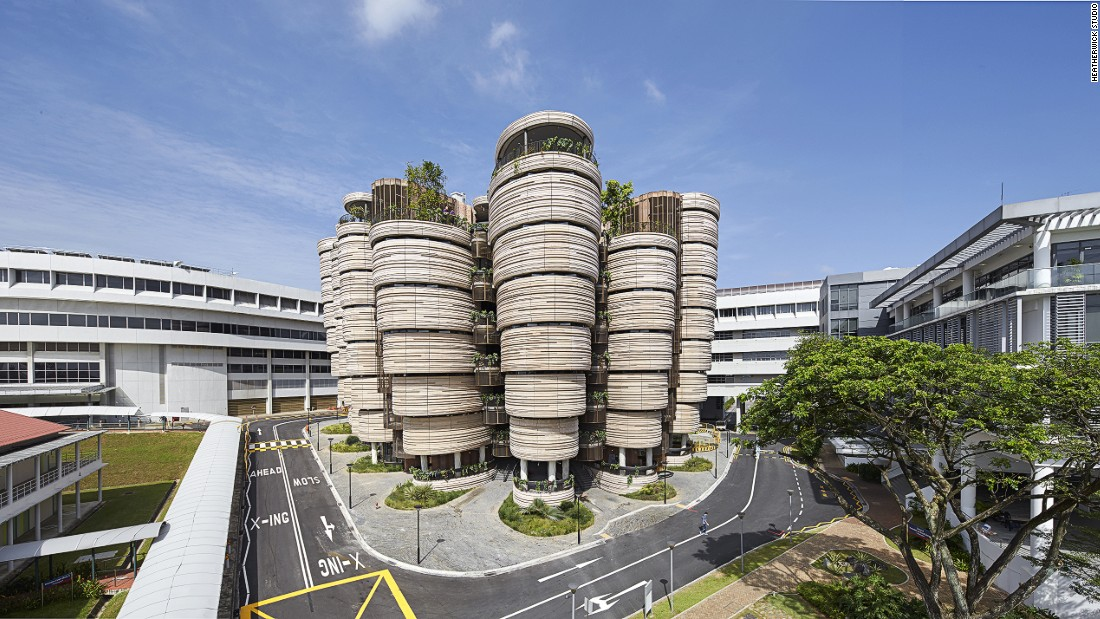 This tapered teaching facility comprises 12 towers, each eight-stories high, built around an expansive central atrium. The curved structure, which is covered in textured concrete panels, was designed to foster more collaborative learning.<br />