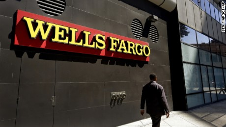 A man passes by a Wells Fargo bank office in Oakland, California. Regulators announced Thursday, September 8 that Wells Fargo is being fined $185 million for illegally opening millions of unauthorized accounts for their customers in order to meet aggressive sales goals.