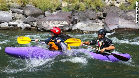 CNN Hero Brad Ludden  and First Descents participant Forest kayak in tandem