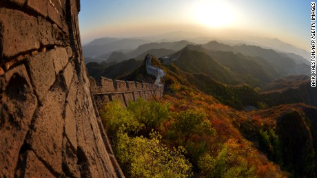 This photo taken on October 20 shows the sun setting over the autumn colours of a section of the Great Wall of China at Jinshanling, Hebei Province. The wall which is a series of fortifications made of stone, brick and rammed earth was subject to a recent archaeological survey that found its total length to be 21,196 km or 13,171 miles.        AFP PHOTO/Mark RALSTON        (Photo credit should read MARK RALSTON/AFP/Getty Images)