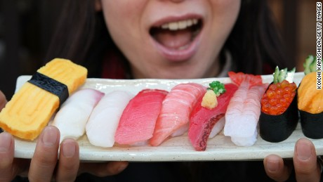 GUJO, JAPAN - FEBRUARY 25:  A Tourist poses with imitation sushi at The Sample Factory on February 25, 2008 in Gujo, Gifu, Japan. Gujo City has more than a 50 percent share of the imitation vinyl chloride samples industry. Replica foods are used in most restaurant window displays in Japan, and are popular as souvenirs for tourists. (Photo by Koichi Kamoshida/Getty Images)