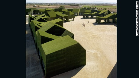 This elementary and primary public school, located in the small town of Roldn, Spain, is wrapped in a green carpet of artificial turf and built on top of a two-meter high perimeter wall to protect it from the region's heavy rains.