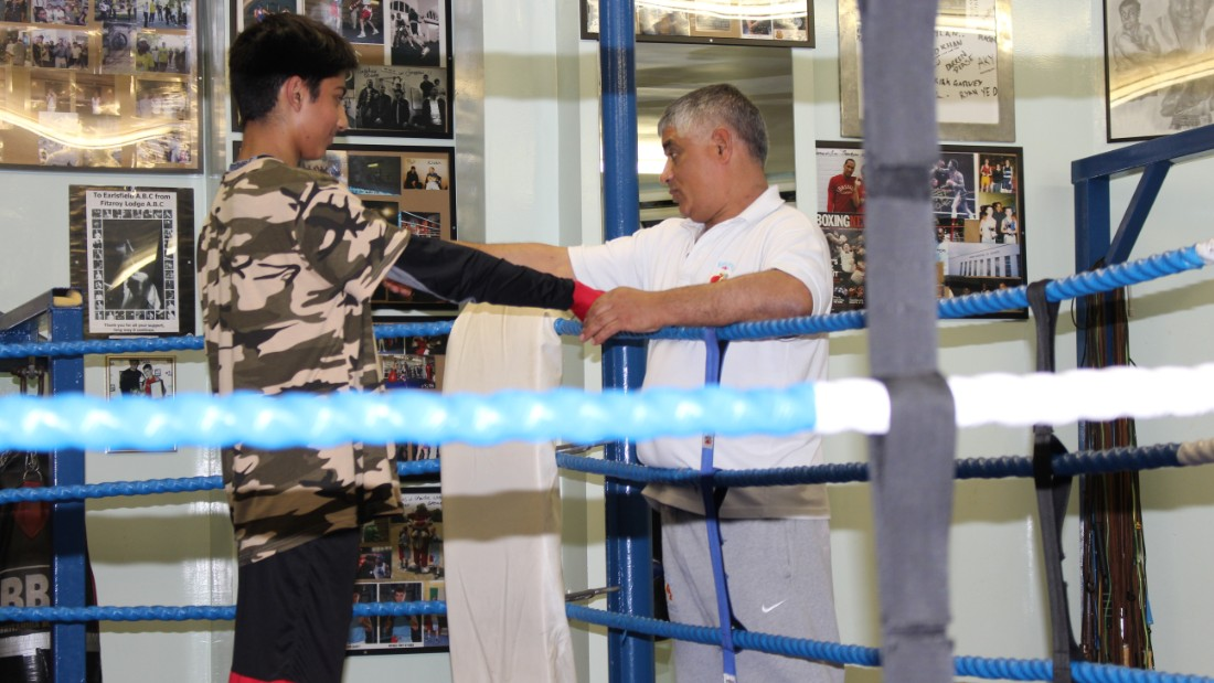 The club opens its doors to amateur boxers of all different levels and both sexes, four days a week. Here, Sid Khan tapes the gloves of a young fighter while offering words of advice.