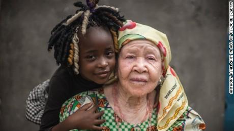 Democratic Republic of Congo (DRC), Kinshasa, Albino grand-mother (Marie Margherite Embongo Hoheka & Dorianne) posing against a grey wall with her black grand-daughter, Kinshasa, (MR)