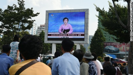 Residents look up at a big screen TV in front of Pyongyang railway station showing television presenter Ri Chun-Hee announcing that the country successfully tested a nuclear warhead earlier in the day on September 9, 2016.
