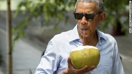 US President Barack Obama drinks from a coconut as he makes a surprise stop for a drink alonside the Mekong River in Luang Prabang on September 7, 2016.