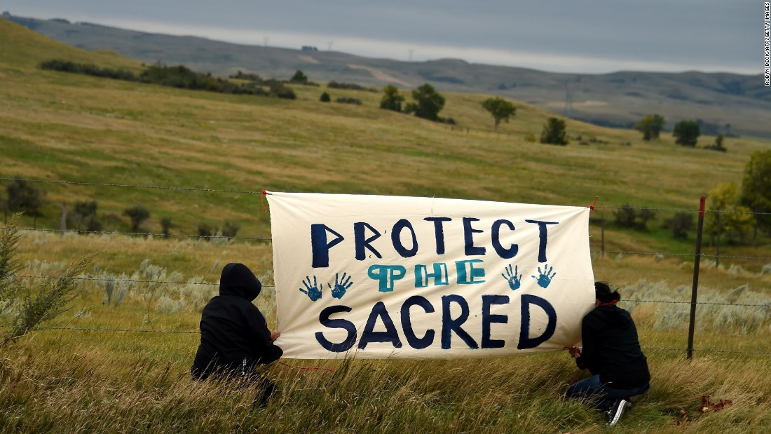 People hang a sign near a burial ground sacred site that they say was disturbed by bulldozers building the Dakota Access Pipeline. Proponents say the project could be an economic boon for the region and potentially change the landscape of the US crude oil supply.