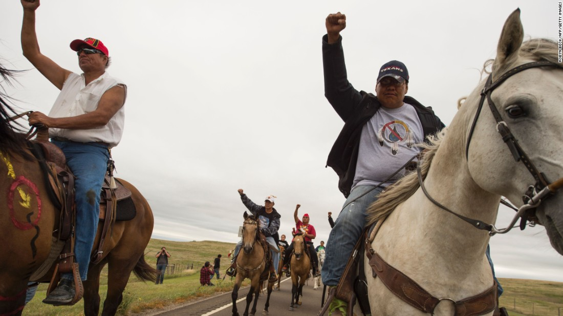 "Native Americans ride with raised fists to a sacred burial ground on September 4, near Cannon Ball, North Dakota. The Standing Rock Sioux Tribe say he pipeline ""threatens the Tribe's environmental and economic well-being, and would damage and destroy sites of great historic, religious, and cultural significance to the Tribe."""