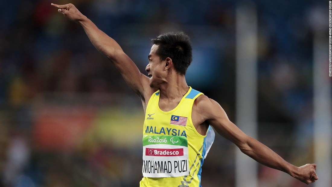 Mohamad Ridzuan Puzi celebrates as he crosses the line in the T36 100m final, winning Malaysia's first ever Paralympic gold medal.