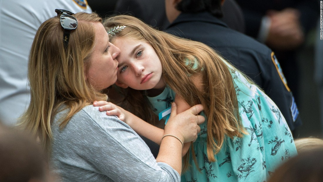 Family members embrace during the 15th Anniversary of September 11 at the 9/11 Memorial and Museum, on September 11, 2016 in New York.