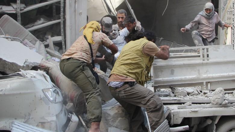 Voluntarios sirios rescatan de los escombros a un sobreviviente después de fuertes bombardeos en la ciudad de Idlib. (Crédito: Getty Images).