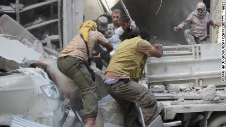 Syrian men evacuate a victim from the rubble of a building following an airstrike on the rebel-held northwestern city of Idlib on September 10, 2016.