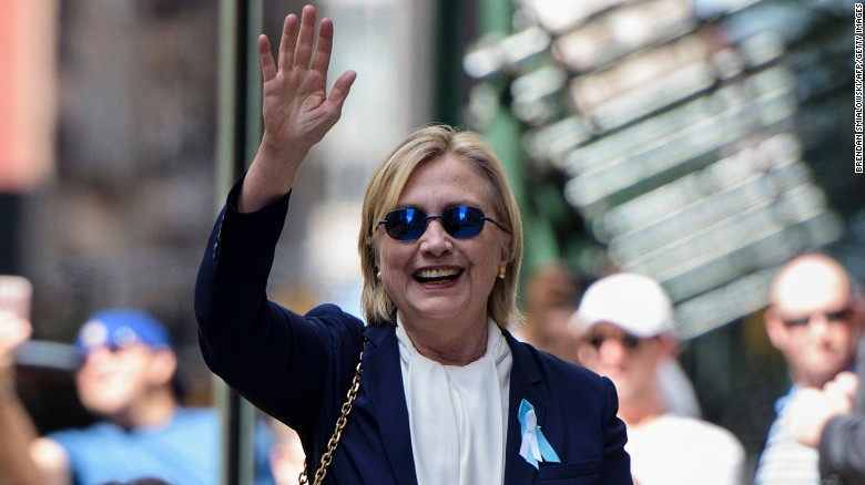 US Democratic presidential nominee Hillary Clinton waves to the press as she leaves her daughter's apartment building on September 11, 2016.