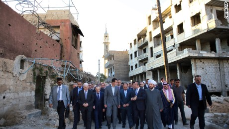 """In this photo released by the Syrian official news agency SANA, Syrian President Bashar Assad, center, walks on a street with officials after performing the morning Eid al-Adha prayers in Daraya, a blockaded Damascus suburb, Syria, Monday, Sept. 12, 2016. Syrian President Bashar Assad says his government is determined to """"reclaim every area from the terrorists, and to rebuild"""" the country. His remarks came just hours ahead of the start of a cease-fire brokered by the United States and Russia. (SANA via AP)"""
