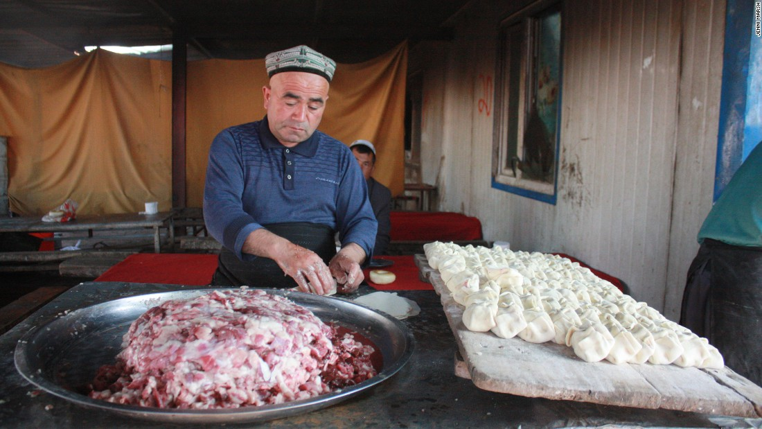 A man makes samsa -- bread parcels with diced lamb inside -- at the market. The parcels are baked inside a stone oven.