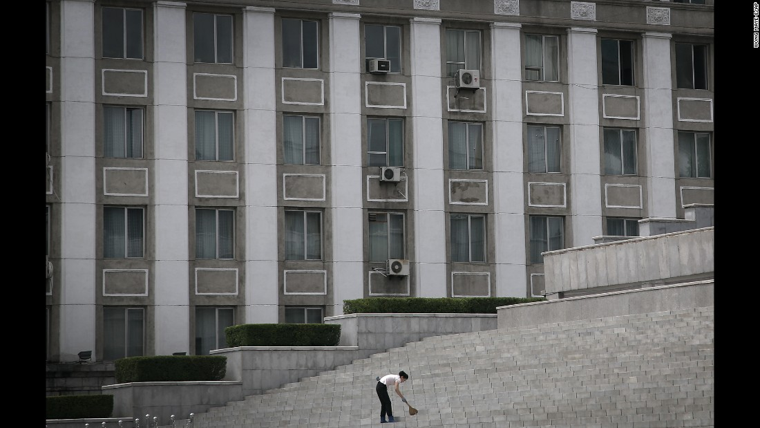 "A woman sweeps stairs at Kim Il Sung Square. ""When I am looking for street features and have opportunities to shoot North Koreans doing what they do, sometimes they don't understand why I am taking their photo,"" Wong said. ""They don't see what is so interesting about what they are doing."""
