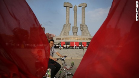 A North Korean man cycles past the Workers' Party monument while framed by red party flags in Pyongyang, North Korea on Sunday, June 19, 2016. North Koreans celebrated the entry of their former leader Kim Jong Il's entry to the Central Committee of the Workers' Party of Korea in 1964. (AP Photo/Wong Maye-E)