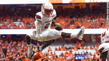 Sep 9, 2016; Syracuse, NY, USA; Louisville Cardinals quarterback Lamar Jackson (8) leaps over Syracuse Orange defensive back Cordell Hudson (20) during the second quarter at the Carrier Dome. Mandatory Credit: Rich Barnes-USA TODAY Sports