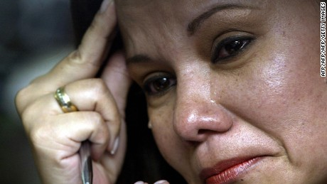 CALI, COLOMBIA:  Fabiola Perdomo, wife of kidnapped deputy Juan Carlos Narvaez, cries during the presentation of a video given as a survival evidence by the Revolutionary Armed Forces of Colombia (FARC) 24 September, 2006, in Cali, Colombia. In the video, which shows twelve deputies kidnapped in April 2002 by the leftist guerrillas, the deputies demand Colombian President Alvaro Uribe to accept the FARC's required demilitarization of two municipalities in south Colombia so as to sign an exchange of 50 kidnapped for 500 imprisoned rebels.  AFP PHOTO / Carlos Julio MARTINEZ  (Photo credit should read CARLOS JULIO MARTINEZ/AFP/Getty Images)