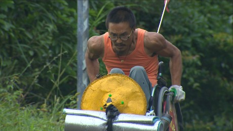 Quan Peng has pushed his wheelchair 3,000 miles across China -- as his bulging biceps prove.