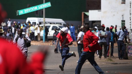 A protester throws a street sign with  Mugabe's name on it during clashes in August.