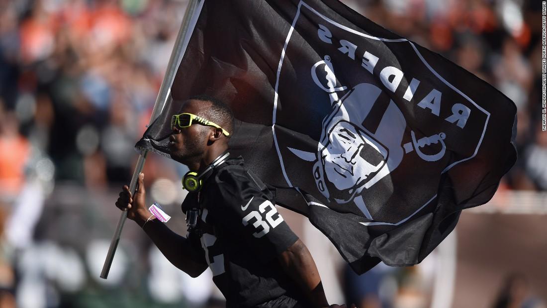 Leeper carries the Oakland Raiders flag in a break in play against the Denver Broncos in November 2014.