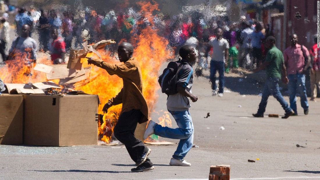 Protesters set up a burning barricade as they clash with police in Harare in August.