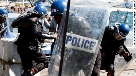 Anti-riot policemen surround an activist at Harare Central Police Station in August.