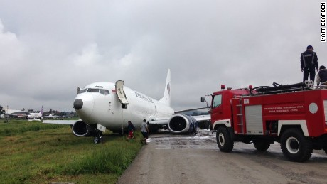 Fire crews attend to a Trigana Air Services flight which violently skidded off the runway.