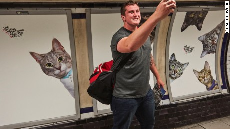 Amused commuter takes quick selfie in front of posters
