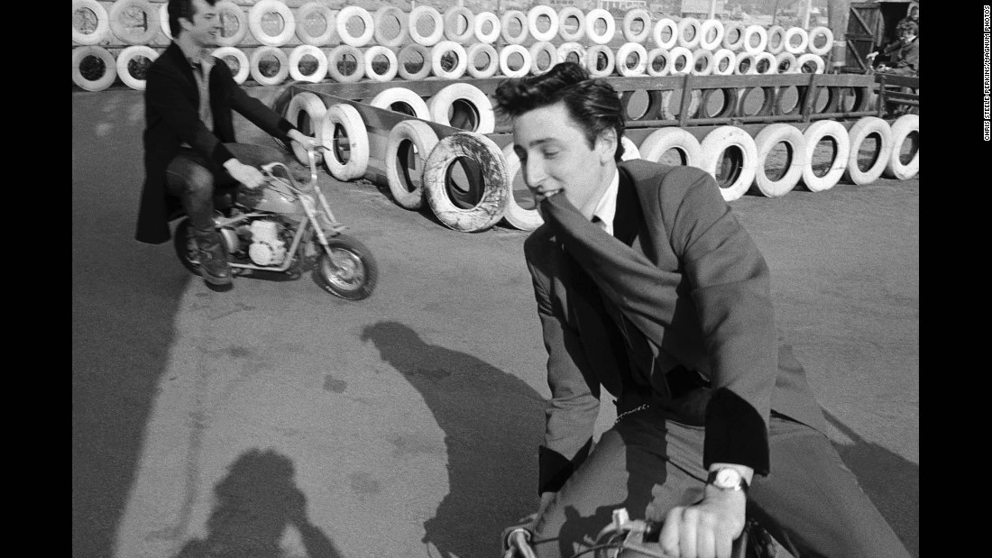 """Two men ride small motorbikes at a fairground. """"The 'Teddy Boys' were the first manifestation of a teenage subculture,"""" Steele-Perkins said."""