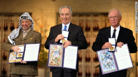 Palestinian leader Yasser Arafat (L), Israeli Foreign Minister Shimon Peres (C) and Israeli Premier Yitzhak Rabin display their Nobel Peace Prizes December 10, 1994 in Oslo, Norway.