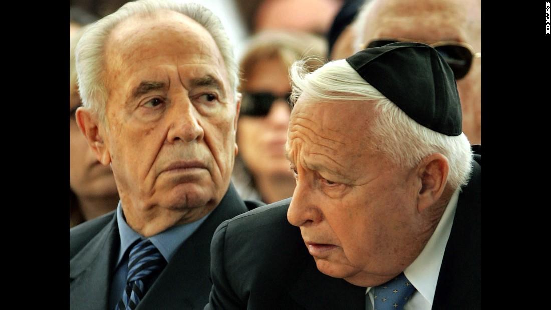 Israeli Vice-Premier Shimon Peres, left, and Israeli Prime Minister Ariel Sharon attend the 32nd annual memorial ceremony for the late Israeli Prime Minister David Ben-Gurion in the southern Israeli kibbutz of Sde Boker on December 7, 2005.