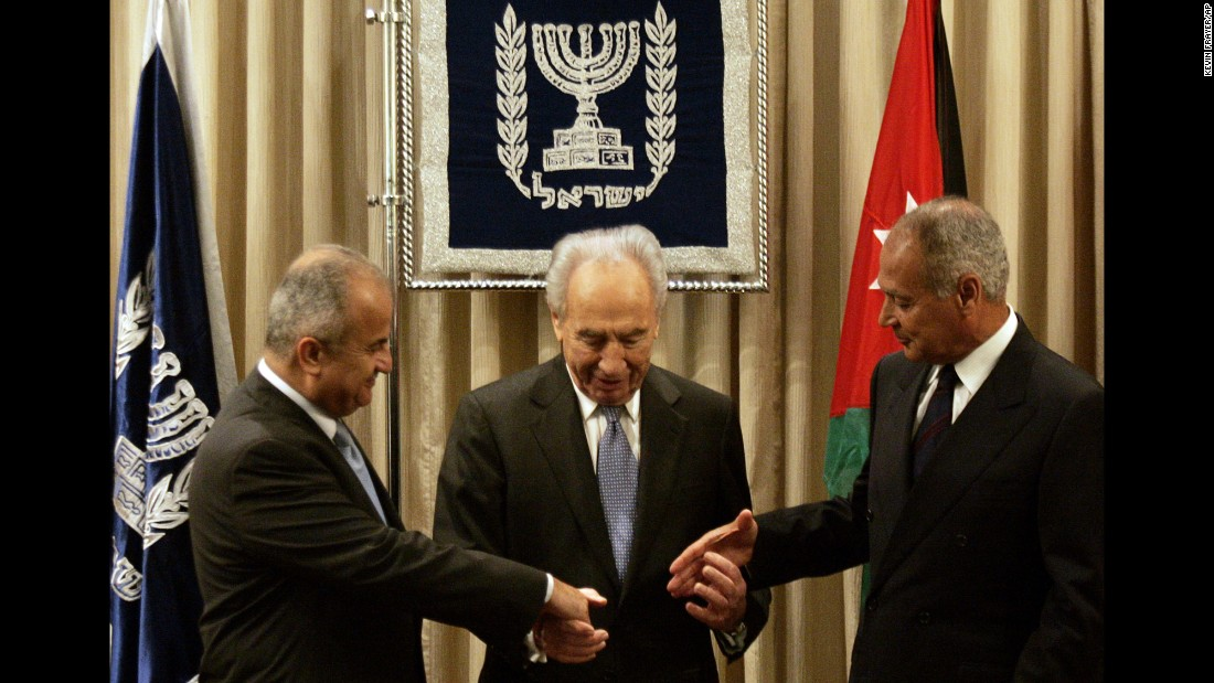 """Israeli President Shimon Peres, center, joins hands with Jordan's Foreign Minister Abdul-Ilah Khatib, left, and Egyptian Foreign Minister Ahmed Aboul Gheit during their meeting in Jerusalem on July 25, 2007.The foreign ministers of Egypt and Jordan made a historic visit to Israel to formally present an Arab peace plan, saying they were extending """"a hand of peace."""""""