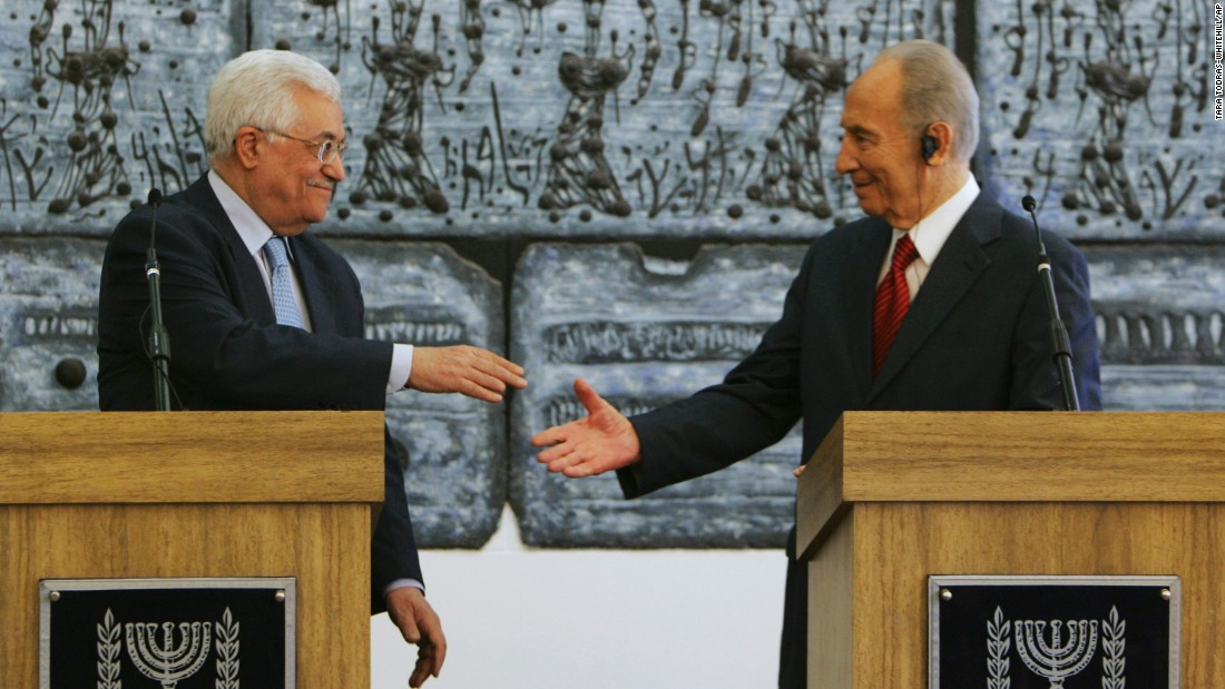 Palestinian President Mahmoud Abbas reaches to shake hands with Israeli President Shimon Peres prior to their meeting in Jerusalem on July 22, 2008. Abbas had threatened to withdraw his forces from West Bank cities unless Israel's military halted its raids into the areas.