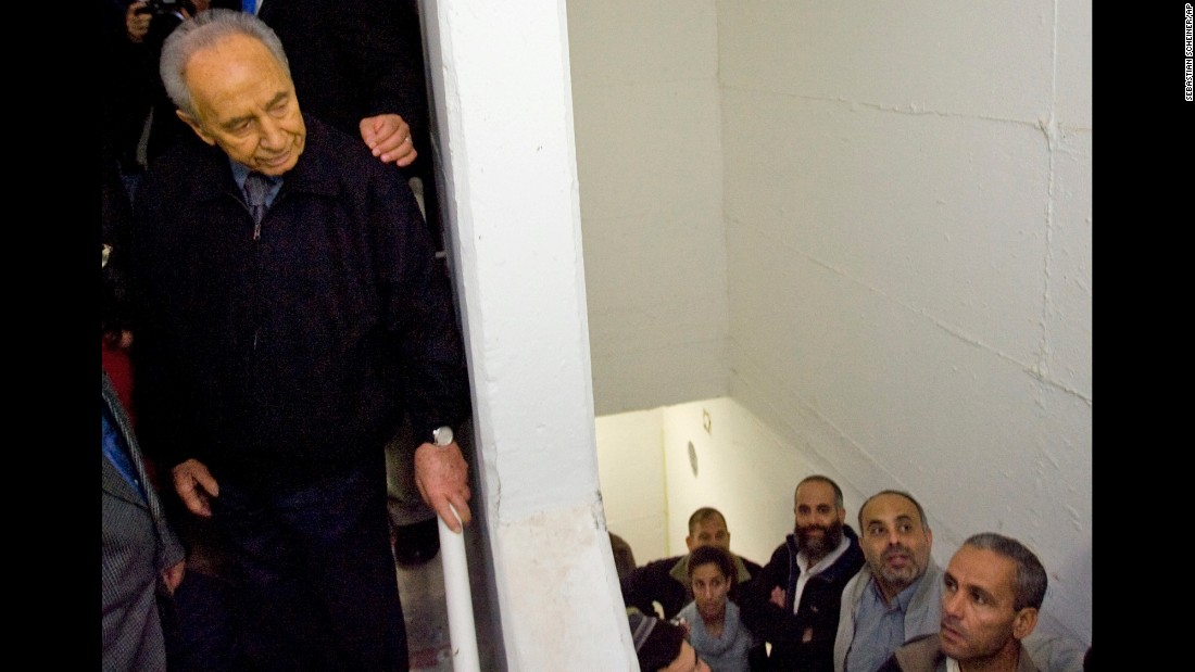 Israeli President Shimon Peres stands inside a shelter as a rocket warning siren blares in the southern Israel city of Ashkelon on December 31, 2008. Israel at the time had rejected mounting international pressure to suspend its devastating air offensive against Palestinian militants.