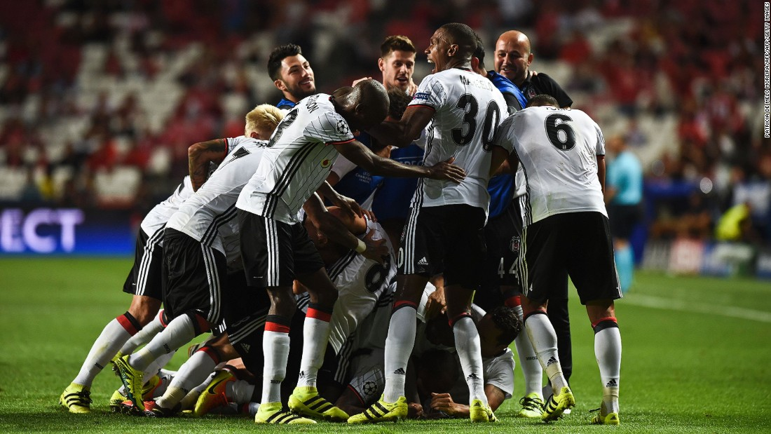 Talisca is buried by his Besiktas teammates after scoring a dramatic long-range free-kick -- converted in the 93rd minute -- to earn a 1-1 draw against parent club Benfica.