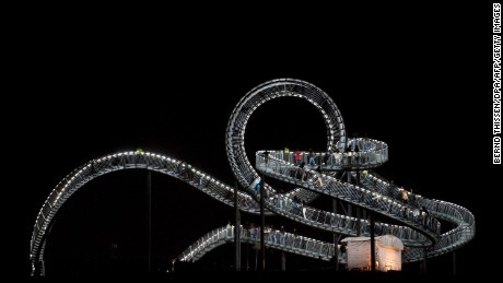 """Visitors walk on the just inaugurated sculpture """"Tiger & Turtle - Magic Mountain"""" by German artists Heike Mutter and Ulrich Genth."""